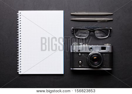 Office desk with photo camera, notepad, glasses, pen and pencil. Top view with copy space