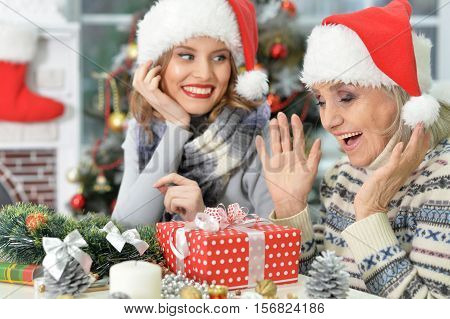 Portrait of senior and young women in Santa hats. Senior woman exited to see her Christmas present