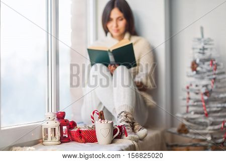 Woman Reading Book In Christmas Decorated Home