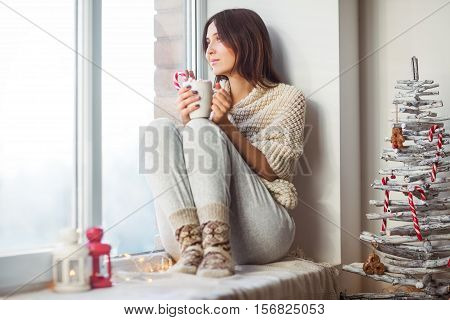 Happy Beautiful Woman Drinking Hot Coffee Sitting On Window Sill In Christmas Decorated Home