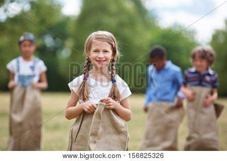 Happy girl with braided hair at sack race smiling