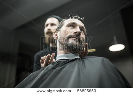 Bearded man in the black cutting hair cape in the barbershop. He has hairgrips on his head. Behind the guy there is a barber with a hair comb. Shoot from the low point. Horizontal.