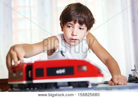 preteen handsome boy play with meccano toy train and railway station