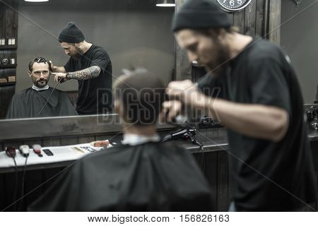 Matchless barber with a beard and a tattoo is cutting the hair of his bearded client in the barbershop. He is using a cutting comb and a hair clipper. They both reflected in a mirror. Horizontal.