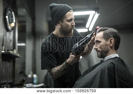 Unequaled barber with a beard and a tattoo is drying the hair of his client in a black cutting hair cape in the barbershop. He is using a black hairdryer and a hairbrush. Horizontal.