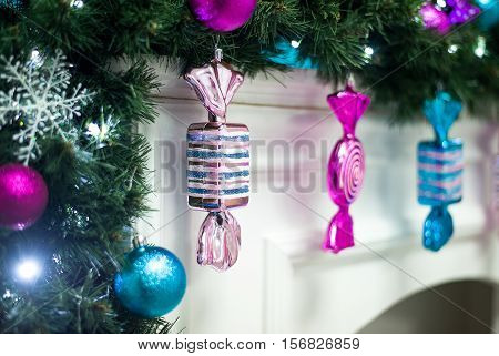 Glass Christmas candy hanging from a garland on the mantelpiece