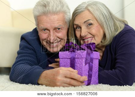 Portrait of happy senior couple celibrating Christmas or New Year, holding gift box