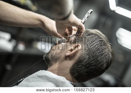 Closeup photo of a barber who is trimming a clients beard with a straight razor on the blurry background of the barbershop. Horizontal.