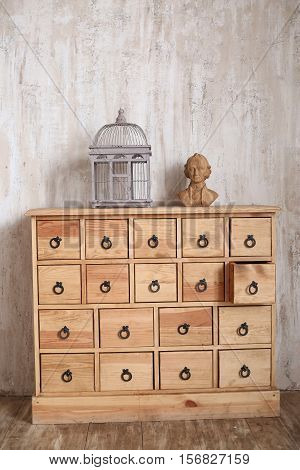 wooden chest of drawers in shabby styled room with bird cage and Mozart bust