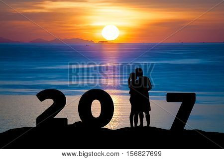Silhouette of romantic couple hug kissing against summer sea beach in sunset twilight sky while celebrating happy new year 2017