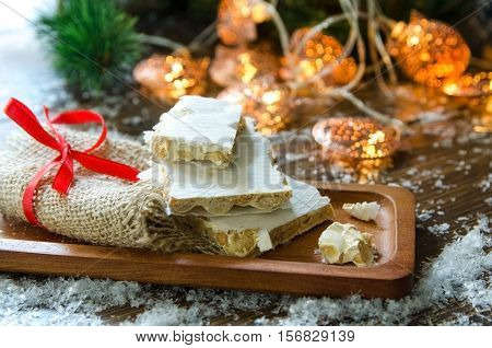 Turron traditional Spanish sweet for Christmas. Almond nougat dessert served in wooden plate on dark background with snow and fir tree.