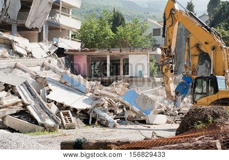 Heavy construction machines demolishing residential building, , color image,