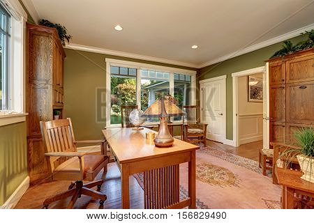 Large home office interior with green olive walls. Furnished with two bookcases desk and two chairs by the window. Northwest USA