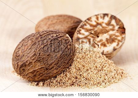 Nutmeg whole and half on wooden plank close up