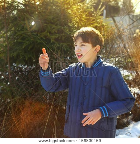 preteen handsome boy toss a coin on the country spring sunny village background