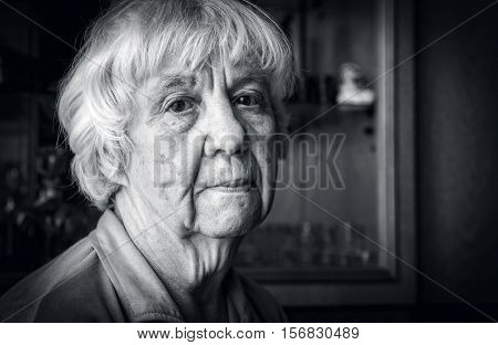 Black and white monochrome portrait of an elderly woman pensive and sad. Her hair is gray.