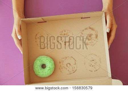 Female hands holding carton box with one donut left