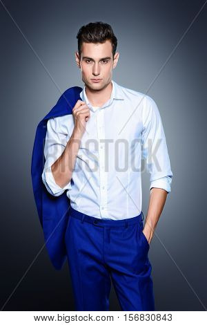 Portrait of a handsome young man in elegant classic suit. Men's beauty, fashion. Businessman. Copy space.