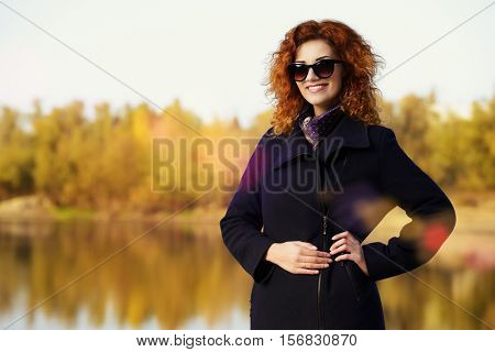 Autumn style. Beautiful happy young woman with bright foxy hair wearing black coat in the autumn park. Beauty, fashion.