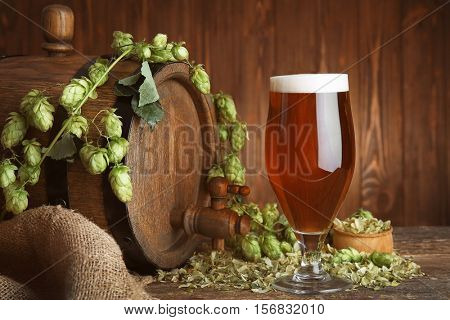 Old barrel, glass of dark beer and hop branch on table against blurred wooden background
