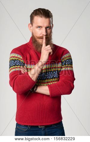Hush. Serious confident bearded hipster man in woolen sweater standing with finger on lips, studio portrait over grey background