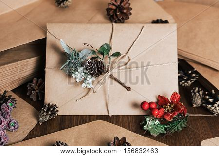 Brown envelope tied with rope. Retro kraft envelop with decorative pine branch with the cone on old wooden table