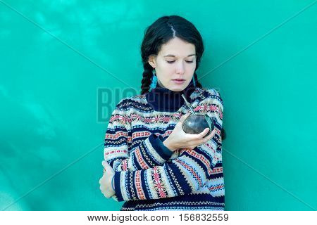Woman wearing woolen snowflakes pattern sweater and turquoise earrings is drinking hot yerba mate