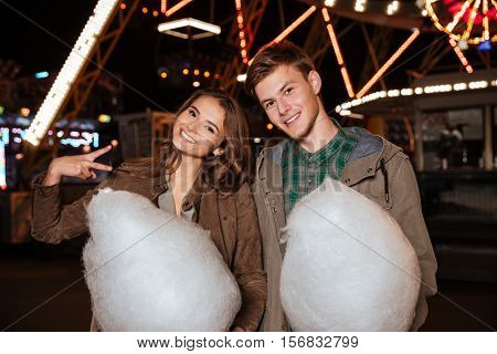 Portrait of happy young couple with cotton candy in amusement park