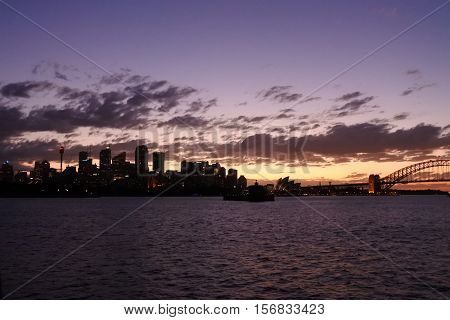 Sydney Australia - October 23 2016: Silhouette of Sydney Skyline across the harbour from North Sydney with city buildings and Sydney Harbour Bridge at dramatic sunset.