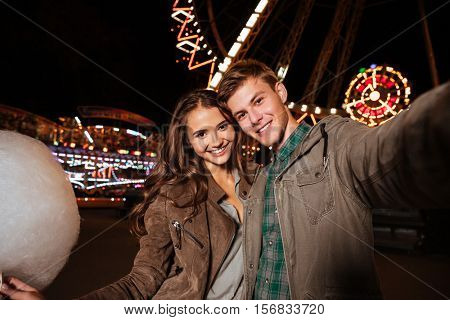 Smiling beautiful young couple with cotton candy taking selfie in amusement park