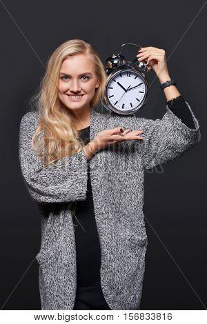 Deadline. Half length portrait of smiling blond woman in warm cardigan showing big alarm clock isolated over grey background