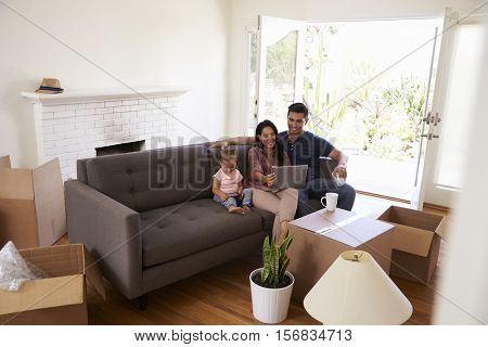 Family Take A Break On Sofa Using Laptop On Moving Day