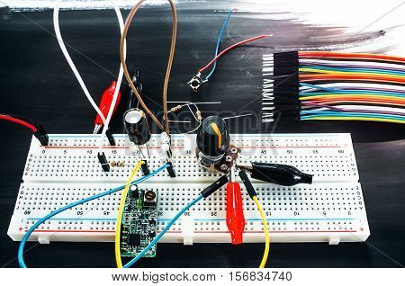 Development of new technological device. Top view on inventor table with breadboard with different connections and set of colorful cables