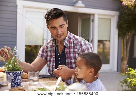 Father And Son Saying Grace Before Outdoor Meal In Garden