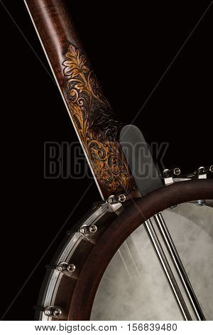 Open Banjo on black background. Carved wooden neck Benjo. Beautiful carved painting.