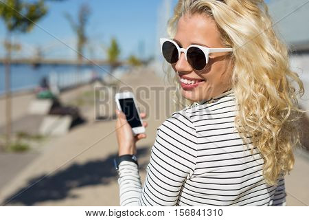 Flirty and pretty woman chatting on smartphone