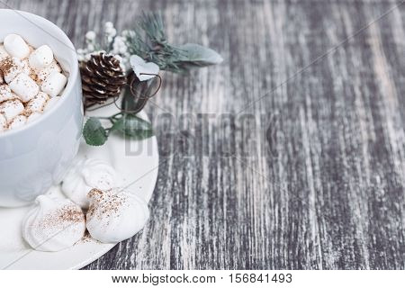 Hot chocolate with marshmallows. Drink in a white ceramic cup with zephyr on wooden table. Decorative pine branch with the cone on plate saucer. Copy space