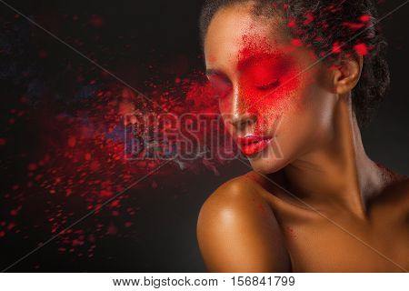 Fashion makeup. Close-up face of a beautiful young woman with splashes of red paint on a black background