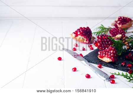 Half pomegranate and pomegranate seeds and a branch of spruce on white wooden background. Copy space