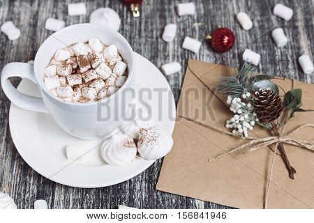 Hot chocolate with marshmallows. Drink in a white ceramic cup with zephyr on wooden table. Envelop with decorative pine branch with the cone