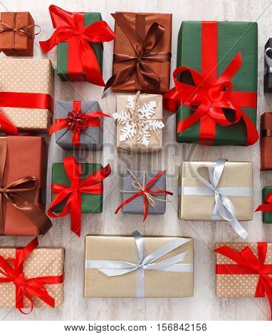 Lots of Gift boxes on white background. Presents in craft and colored paper decorated with red satin ribbon bows. Christmas and other holidays concept.