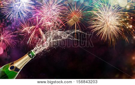 Bottle of champagne over fireworks background. Celebration concept, free space for text
