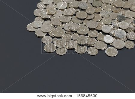 Pile of UAE dirham coins on dark background