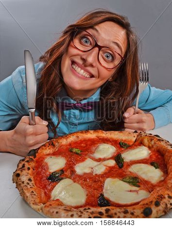Expressive nerd woman sitting ready to eat pizza holding fork.