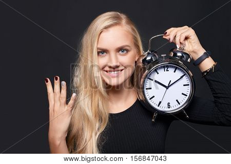 Hand counting - number four. Smiling woman holding big alarm clock showing four fingers, portrait over grey background