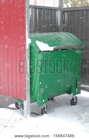 Standard green garbage container on the background of winter snow.