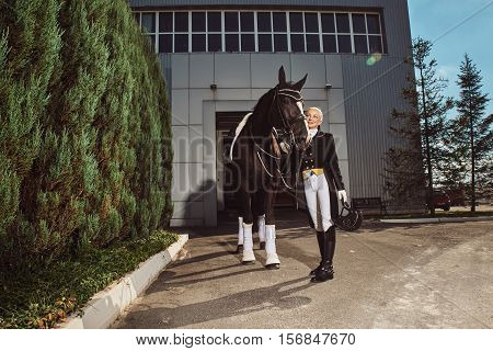 woman jockey with her horse in uniform for Dressage