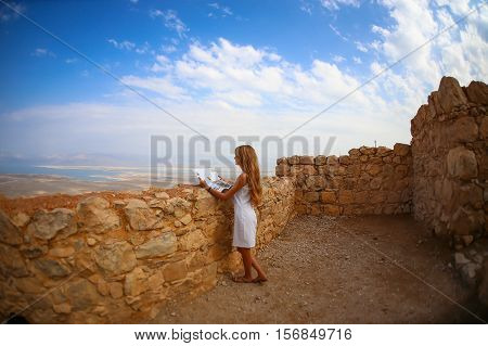 tourist girl standing on top of Mount Masada in Israel. Traveler holding map of the area