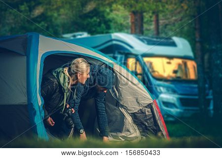 Couples Tent Camping. Men and Woman in Their 30s Camping in the Small Tent with Motorhome in the Background.