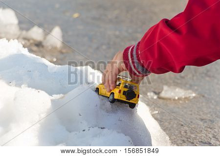 A small child plays with a toy in a snow pile. The kid holds up the car. Toy taxi yellow with black details. Sleeve jacket in red. The background is blurred.